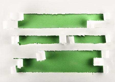 Torn paper holes with green background. photo
