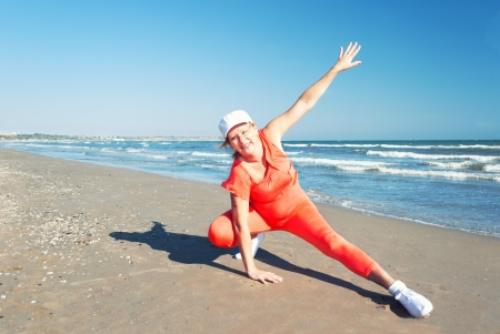 Mature woman enjoying her fitness exercises on a beach.