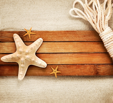 starfish: Few marine items on a wooden boards against sandy background. Stock Photo
