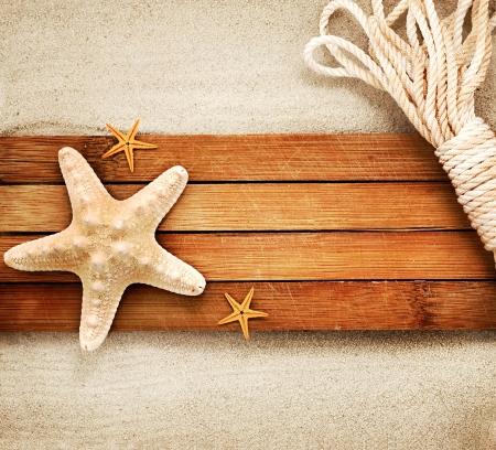 estrella de mar: Pocos elementos marinos en una placa de madera contra el fondo arenoso.