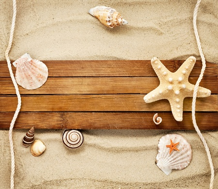 Few marine items on a wooden boards against sandy background. Foto de archivo