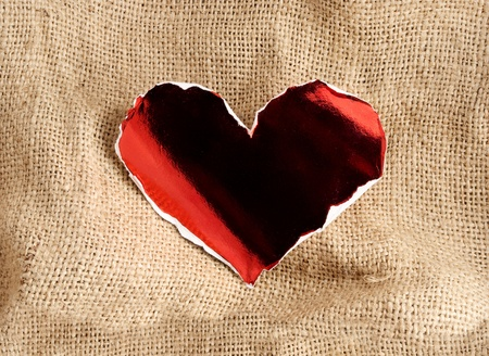 Red glossy paper heart with torn edges on a sackcloth background  photo