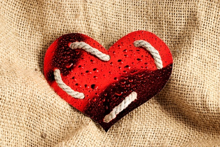 Red glossy paper heart graced of rope and water drops on a sackcloth background  photo