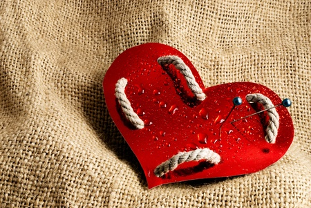 Red glossy paper heart graced of rope pierced with pins and covered of water drops on a sackcloth background  photo