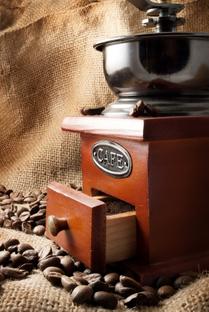 Classic coffee grinder full of coffee beans on a sackcloth background  photo