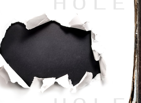 Breakthrough paper hole on white  photo