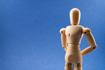 waiting posture: Classic wooden dummy in patiently waiting pose over blue background.