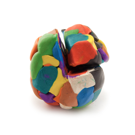 Colorful pieces of plasticine molded together in a sphere with cut segment over white background. Stock Photo