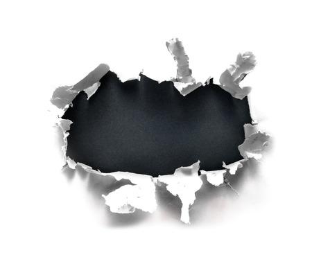 Breakthrough paper hole with gray background. Archivio Fotografico