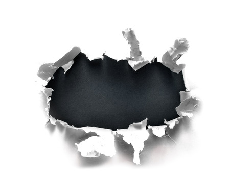 Breakthrough paper hole with gray background. Stock Photo