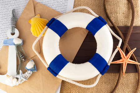 sea life centre: Classic lifebuoy and few marine items over sackcloth background. Stock Photo
