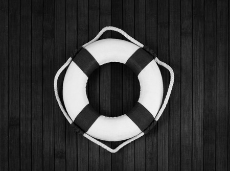 sea life centre: Classic lifebuoy on a wooden planks. Monochrome.