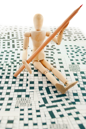 mental object: Classic wooden dummy with red pencil and crossword puzzles. Stock Photo