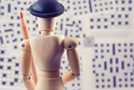 clues: Classic wooden dummy with red pencil and crossword puzzles. Stock Photo