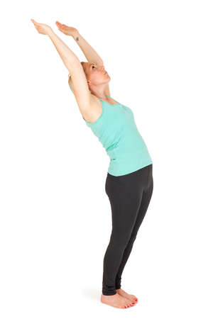 pada: Full body view of a young blond woman in yoga exercise Standing bend forward step 3 in front of white background with light shadow. Stock Photo
