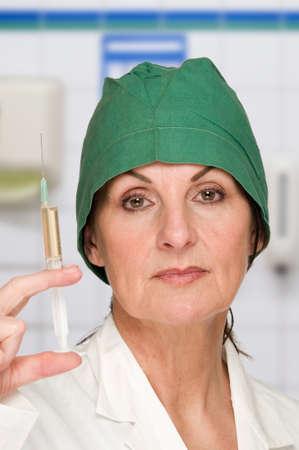 enfermera con cofia: doc muestran la vertical_background jeringa Foto de archivo