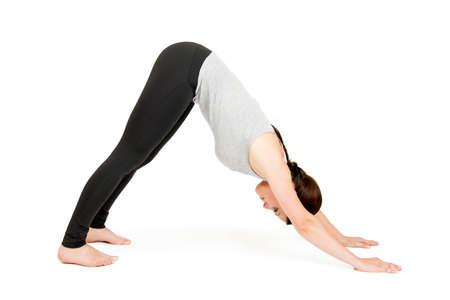 Ganzkörper-Ansicht einer jungen schwarzhaarigen Frau auf weißen Hintergrund in Yoga-Position herabschauender Hund (adho muka shavasana)