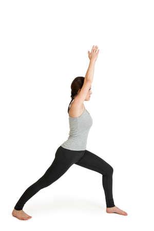 mit: Ganzkörper-Ansicht einer junger schwarzhaarigen Frauen bei der Yoga-Übung friedlicher Krieger (Varabhadrasana) vor weißen Hintergrund mit leichten Schatten