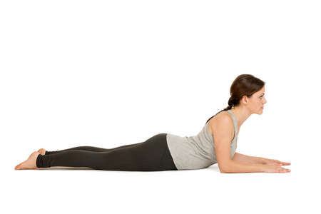 Seitliche Ganzkörper-Ansicht einer jungen Frau weißen Hintergrund die Yoga-Position die Sphinx (Salamba Bhujangasana) in der Grundstellung zeigend. Stock Photo