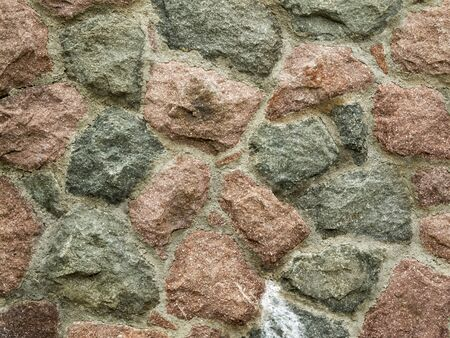 Full frame view of a brick-walled field-stone wall with cement joints.