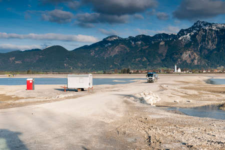 Empty forggensee with construction vehicle and toilet house