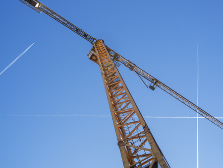 Tower crane with blue sky and contrails