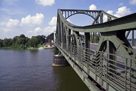 View of the Glienicke Bridge from east to west at blue sky with single clouds.