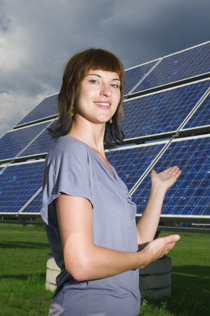 Side Torso View Of A Young Woman With Hands On A Photovoltaic Panels Standing Behind Her Smiling And Smiling Friendly At The Camera.