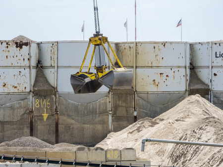 Open excavator bucket with rope guide over a gravel mountain floating with silos in the background.
