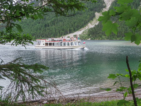 Excursion Ferry MS Wilhelm at a narrow point on the Plansee in Austria in front of a steep bank wall and rockfall.