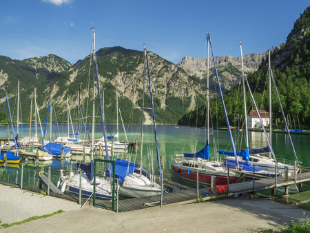View of the marina with small sailing boats on the Plansee in Austria with blue sky against a mountainous backdrop.