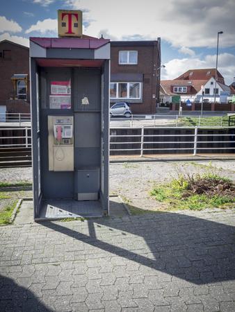 Carolinensiel, Germany - April 22, 2017: One of the last open public telephone booths in Carolinensiel.