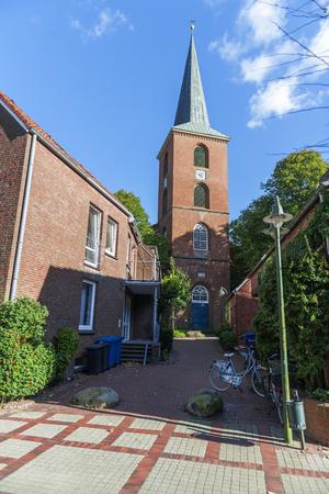 Blick durch eine kleine Gasse auf den Turm der St.-Magnus-Kirche in Esens  Ostfriesland. Stockfoto