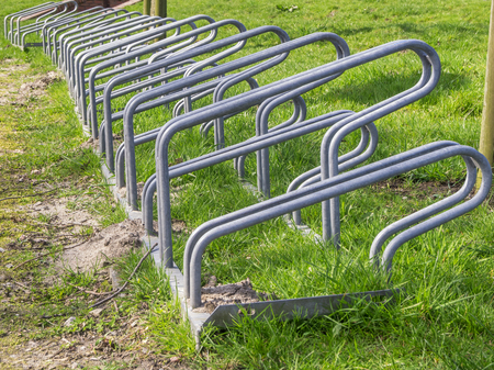 Close-up of a mounted bicycle rack on green grass field.