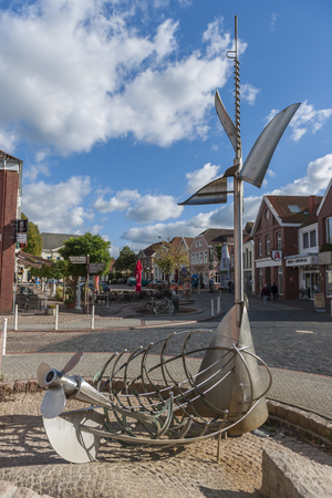 Tidebrunnen by the metal artist Albert Sous overlooking the market in the city of Esens in fine weather.