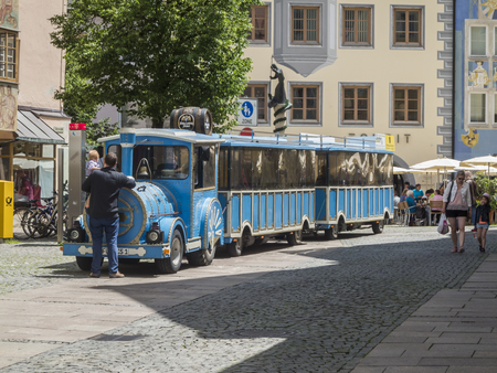 Fussen, Germany - July 03, 2017: Blue city tour with tractor and two trailers at the stop. City fountain. Knight street with passers-by. Redactioneel
