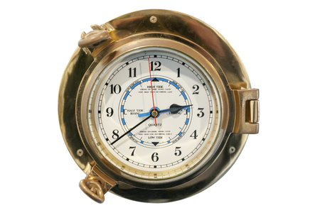 Frontal view of an old mechanical tide clock in a brass case. Redactioneel