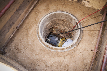 Rehabilitation work on an exposed sewer with manhole and automatic feed device for lining the canal.