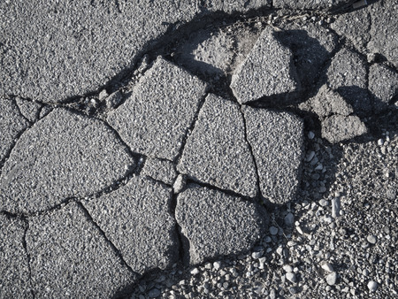 Detail-view of a cracked aspalt layer on a side street. Stockfoto