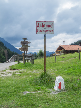 Schwangau, Germany - July 11, 2018: Border sign and landmark between Germany and Austria on the Salober-Alm photographed from Germany. Redactioneel