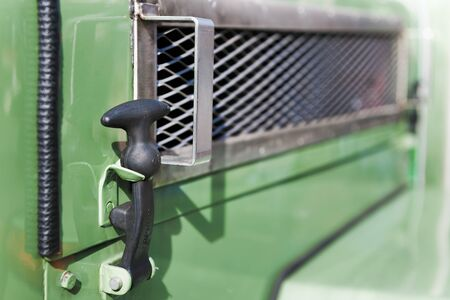 Hood holder made of black rubber on the side of an old green tractor. Imagens
