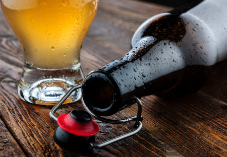 intoxicate: Empty bottle lie near glass beer. Close-up Stock Photo