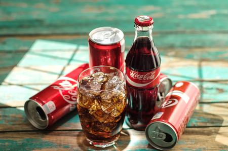 cola canette: MINSK, BELARUS-26 AOÛT 2016: Verre de Coca-Cola avec de la glace, des canettes et une bouteille de Coca-Cola sur fond en bois. Coca-Cola est une boisson carbonatée vendue dans les magasins, à travers le monde.