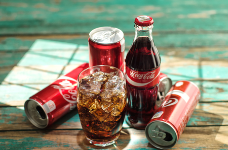 minsk: MINSK, BELARUS-AUGUST 26, 2016: Glass of Coca-Cola with ice, can and bottle of Coca-Cola on wooden background. Coca-Cola is a carbonated soft drink sold in stores, throughout the world. Editorial