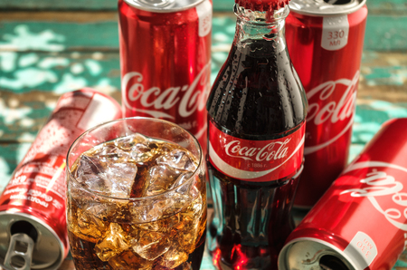 fizz: MINSK, BELARUS-AUGUST 26, 2016: Glass of Coca-Cola with ice, can and bottle of Coca-Cola on wooden background. Coca-Cola is a carbonated soft drink sold in stores, throughout the world. Editorial