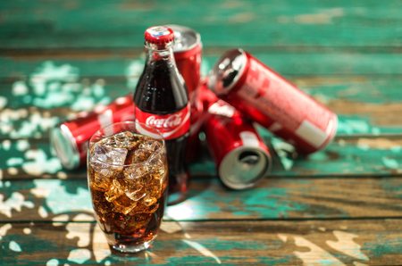 the throughout: MINSK, BELARUS-AUGUST 26, 2016: Glass of Coca-Cola with ice, can and bottle of Coca-Cola on wooden background. Coca-Cola is a carbonated soft drink sold in stores, throughout the world. Editorial