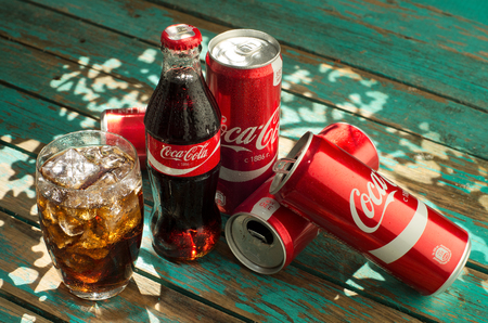 MINSK, BELARUS-AUGUST 26, 2016: Glass of Coca-Cola with ice, can and bottle of Coca-Cola on wooden background. Coca-Cola is a carbonated soft drink sold in stores, throughout the world. Editorial