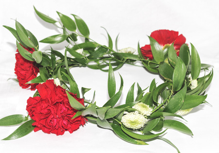 Floral wreath with red carnations, chrysanthemum, ruscus on light background