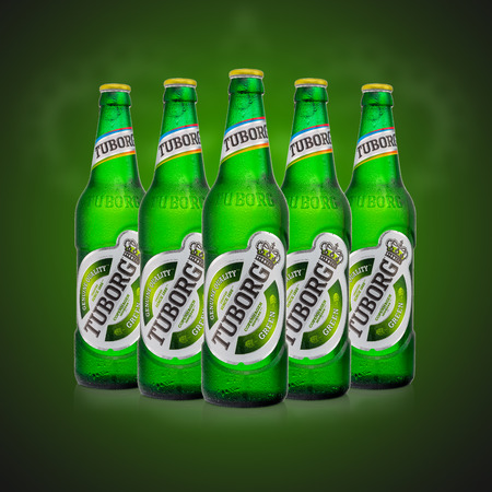 MINSK, BELARUS - AUGUST 23, 2016: Editorial photo of five cold bottles Tuborg glass beer on green background. Tuborg northern suburb of Copenhagen, Denmark. It has been part of Carlsberg Group since 1970 Editorial