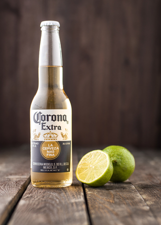 MINSK, BELARUS - MARCH 27, 2017: Editorial photo of bottle of Corona Extra Beer with lime on dark wooden background. Corona is produced by Grupo Modelo with Anheuser Busch InBev.